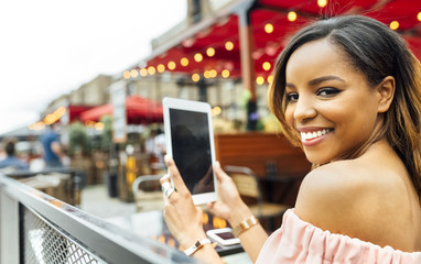 Smiling woman with tablet in the city