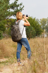 Young lady walking on a rural road with digital camera