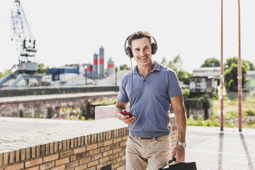 Businessman walking in the city, using smartphone and headphones