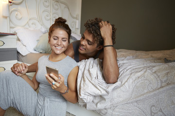 Young couple sitting on bed, talking, using smartphone