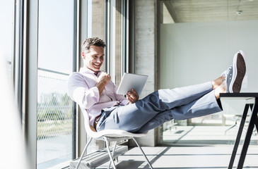 Businessman sitting at desk with feet up, using digital tablet