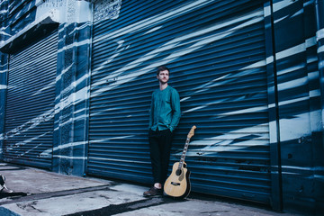 Hipster musician is standing with a guitar on blue graffiti background.