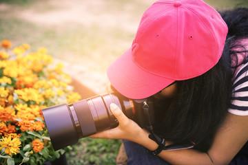 Girl taking photograph of yellow flower using macro lens.