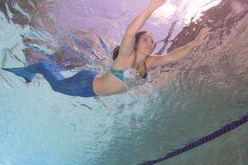 Model in a pool wearing a mermaid's tail.