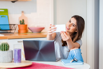 Young woman sitting on chair at table on laptop and taking a selfportrait in a modern decorated home interior.