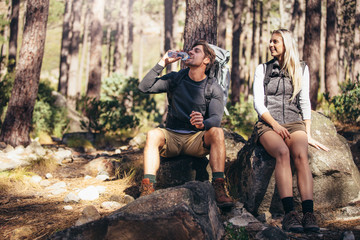 Hiking couple relaxing sitting on rocks during trekking