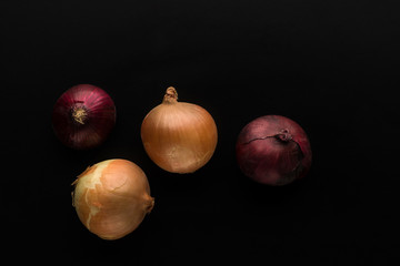 four onions of red and gold colours on a black background top view