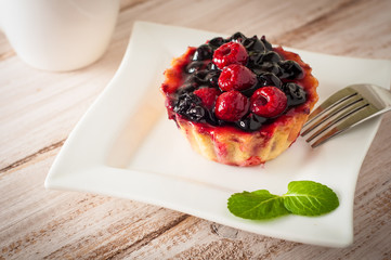 Fresh berry tartlet or cake filled with custard, raspberry, blueberry redcurrant and blackberry delicious dessert, easy diet. Close up