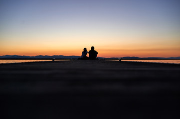 Couple sitting on a pier at sunset silhouette