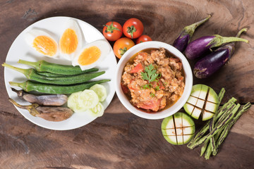 Thai Northern food (Nam Prik Ong) with vegetables on wooden background,spicy tomato with pork,red chili dip,Northern Thai dipping sauce
