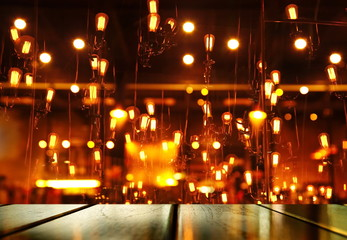 top of wood table with blur light orange lamp of bar or pub for party in the dark night background