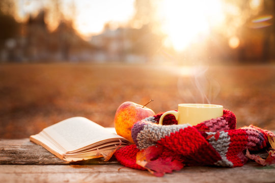 Open book, apple and yellow tea mug with warm scarf