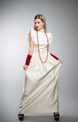 Girl model in a long white dress in the studio.