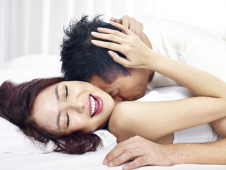 intimate asian couple kissing in bed