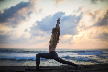 Woman exercising yoga by the sea