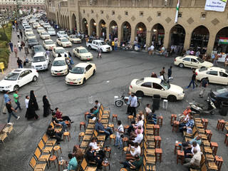 Kurdish people sit at a coffee shop on a street in Erbil