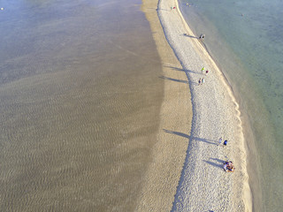High angle view of people walking on sandbar amidst sea