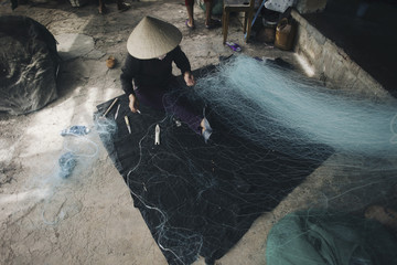 Person in conical hat repairing fishing net