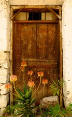 Old wood door with flowers in Kritsa village, Crete, Greece