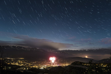 Scenic view of star trails over illuminated cityscape at night