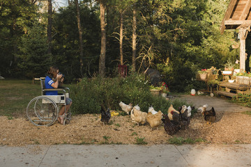 Girl photographing hens while sitting on wheelchair