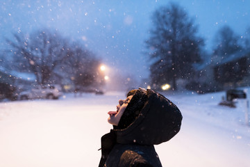 Boy catching snowflakes on tongue