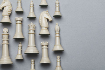 Chess game pieces on a grey background. Strategy concept