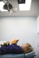 Girl with toy lying on hospital bed looking at equipment in ceiling