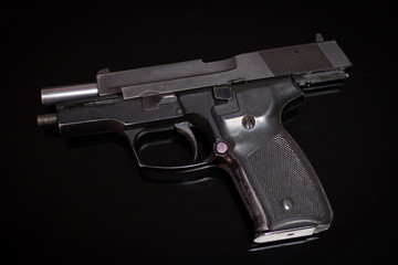 Handgun in the rear position isolated on black