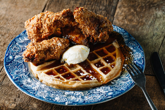 Chicken wings and waffles served with butter and blackberry syrup