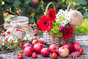Herbstdekoration mit roten Äpfeln,Herbstblumen im Weidenkorb und Kerze im Glas