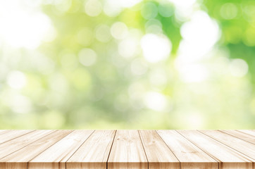 Empty wooden table top front of morning light with blurred natural abstract background.