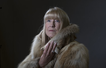 Portrait image of a mature woman in a fur coat, taken on a black background