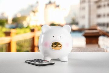 Piggy bank with calculator on table. Vacation concept