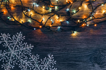 Garland with colored lights and snowflakes on a wooden background. Christmas background