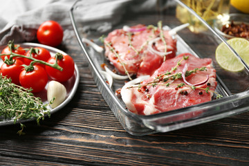Wall Mural - Baking dish with fresh raw steaks and vegetables on table