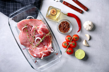Composition with fresh raw steak in baking dish on table
