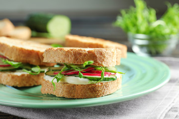 Plate of tasty sandwiches with fresh cucumber on table
