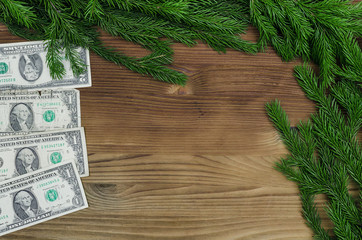 Dollars money laying in Christmas fir tree branches on burnt wooden board surface background with copy space. Christmas decorations.