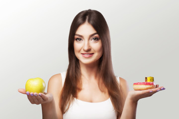 Healthy food. The woman is losing weight. A young girl hesitates between choosing food or sports. The Concept of Health and Beauty. On a gray background.