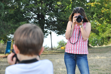 Mom  make photos of her little son. Woman photographer taking photo of little boy