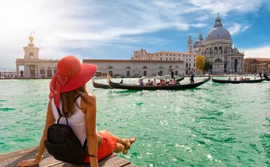 Attraktive Touristin am Canal Grande in Venedig schaut auf die Basilica Santa Maria della Salute