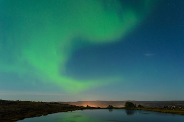 Autumn Aurora, the polar lights in the sky over the river,lake and hills at night .