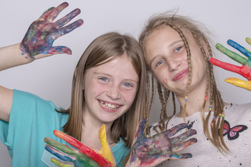 Portrait two young girls and hands painted in watercolors, close up