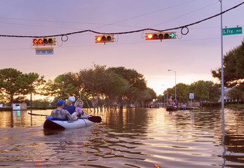 HOUSTON, USA - SEPTEMBER 2, 2017: Working traffic lights over flooded Houston streets and boats with people at sunset