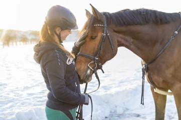 Frau Reiterin streichelt Hannoveraner Pferd vor Schneelandschaft