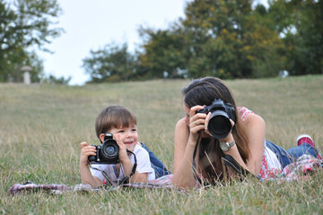 Mom and son make photos with digital camera. Woman photographer taking photo together with her son