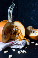 sliced fall pumpkin with seeds on dark background