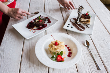 Presentation of delicious desserts in restaurant. Napoleon and chocolate cake with tiramisu serving on wooden table by waiters
