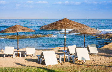 Mediterranean beach with empty sunbeds in the morning, Paphos, Cyprus